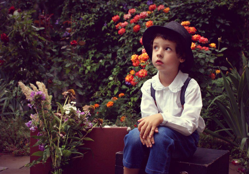 Jung mit Hut vor Blumen, ein Träumer in Gedanken versunken
