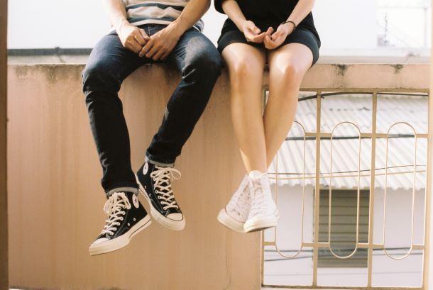 Frau und Mann sitzen auf einer Balustrade